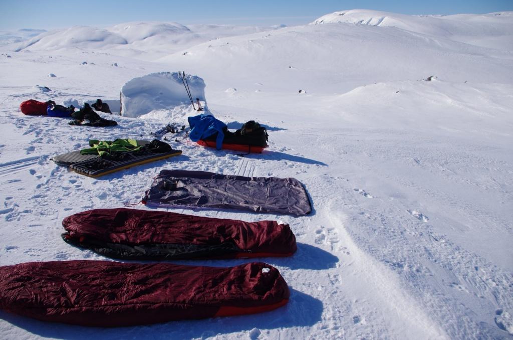 Isomatten, Schlafsäcke und Ausrüstung zum Trocknen im Schnee