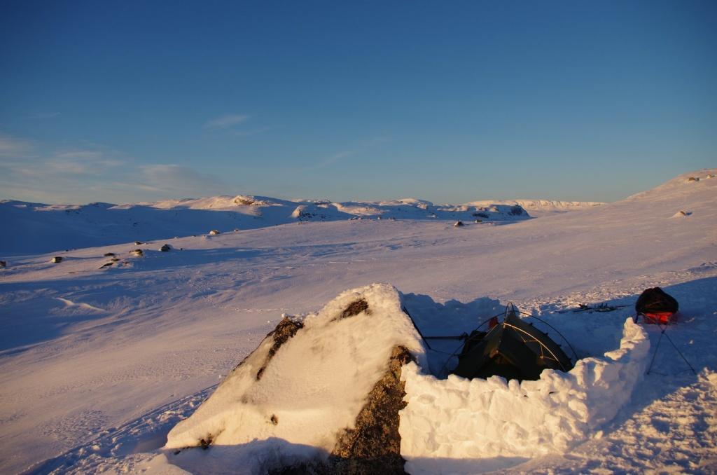 Biwakplatz mit Schneemauer vor verschneiten Hügeln