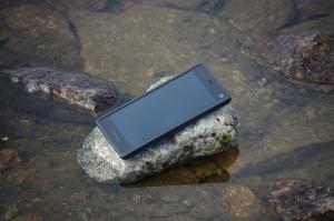 Fairphone 2 auf Stein im spiegelglatten Wasser