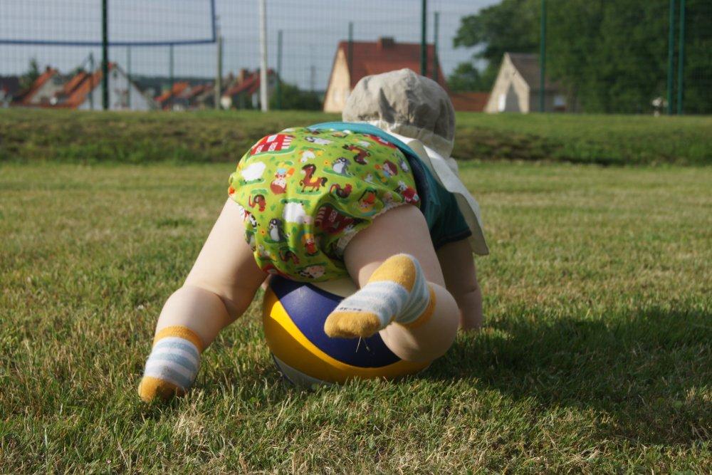 Baby krabbelt in Stoffwindel mit Ball über die Wiese