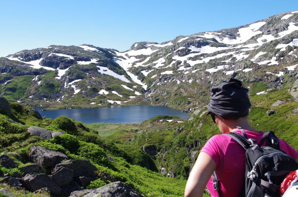 Grüne Berglandschaft in Südnorwegen mit Schnee und See