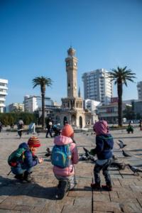 Der Uhrenturm von Izmir mit Tauben, Kindern und Palmen bei komplett blauem Himmel
