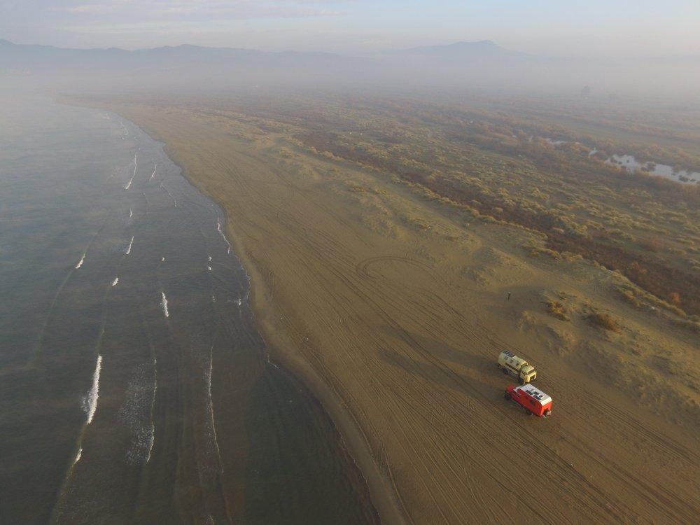 Leichte Brandung am Mittelmeer mit Dünenlandschaft im Nebel und breitem Sandstrand auf dem zwei Allradwohnmobile stehen.