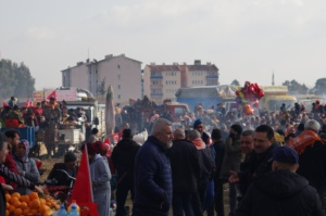Eine Menschenmenge aus Einheimischen und Zugereisten umringt in Jacken den Festplatz von İncirliova in der Türkei.