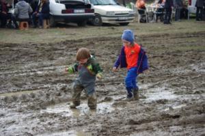 Zwei Kinder spielen begeistert im knietiefen Schlamm und tragen dabei Gummistiefel.