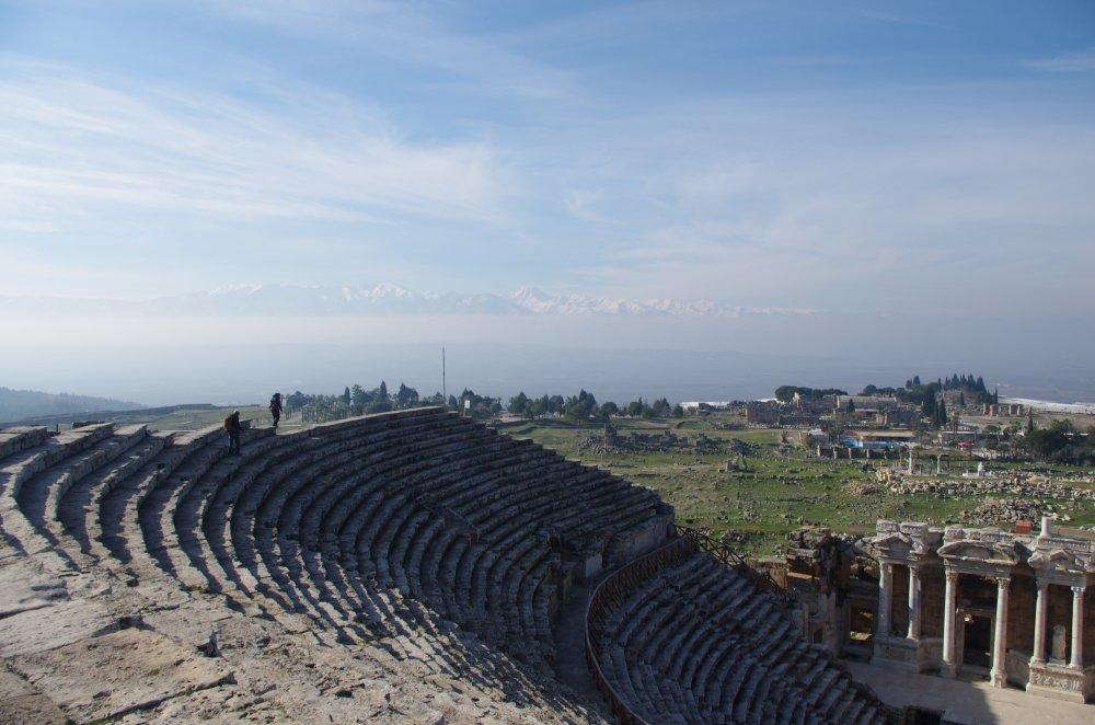 Historisches Theater im Vordergrund mit den Trümmern des antiken Hierapolis im Hintergrund bei locker bewölktem Himmel.