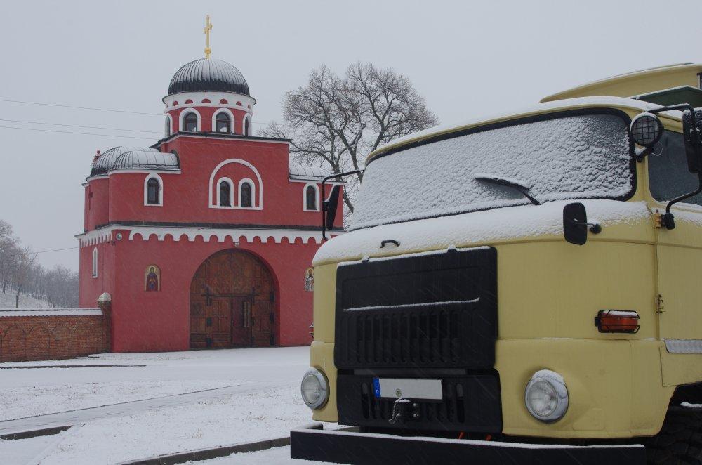 Prunkvolles rotes Eingangsportal zum Kloster mit gelbem IFA L60 im Vordergrund. Über allem liegt eine dünne Schneeschicht.