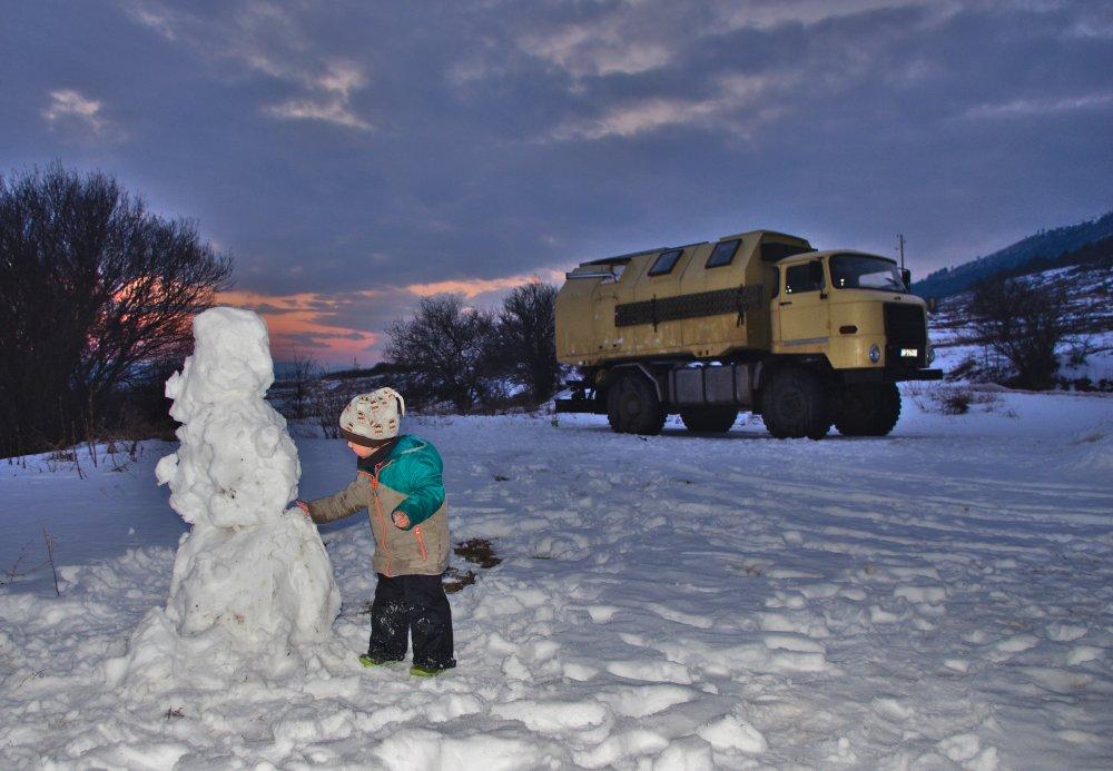 Schneelandschaft auf dem Balkan mit Schneemann und Kind im Vordergrund und dahinter der IFA L60 Allradlaster.